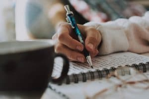 designing your author platform - woman holding pen and writing in notebook with a mug close at hand
